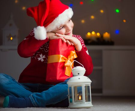 christmas light: Cute little boy in red hat with gift sitting near latern and waiting Santa Claus Stock Photo