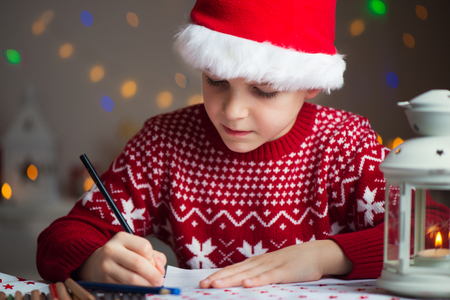 letter writing: Christmas helper child writing letter to Santa Claus letter in red hat Stock Photo