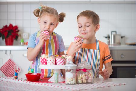 decoracion de pasteles: Niño pequeño lindo y chica preparar galletas de Navidad en casa Foto de archivo