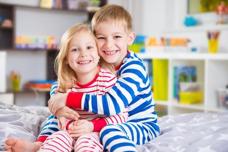 ragazza innamorata: Piccolo fratello carino e sorella in pigiama a casa