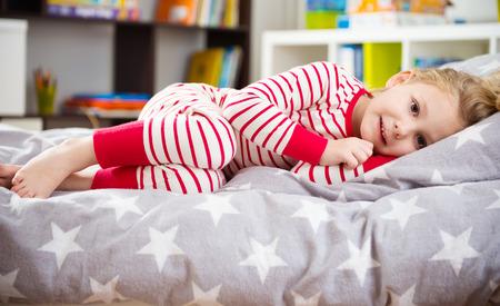 Cute little girl in pajama sleeping in bed Foto de archivo