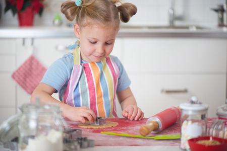 baking christmas cookies: Pretty little girl baking Christmas cookies at home