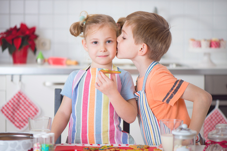 kiss biscuits: Cute little boy and girl preparing Christmas cookies at home Stock Photo