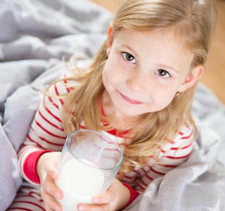 vaso de leche: Niña linda con el vaso de leche en la recamara