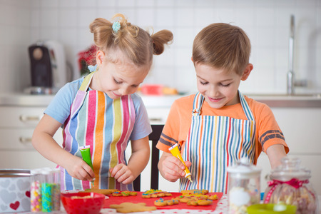 apron: Cute little boy and girl preparing Christmas cookies at home Stock Photo