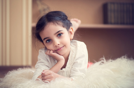 Portrait of cute little latino girl lying on wite carpet Banque d'images