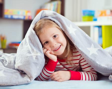 ni�as sonriendo: Ni�a bonita en ropa de dormir miente bajo la manta Foto de archivo