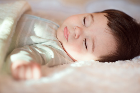 Closeup portrait of sleeping baby covered with knitted blanket Stock Photo