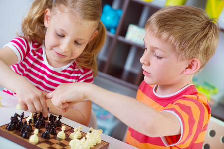 Two cute children plaing chess at home
