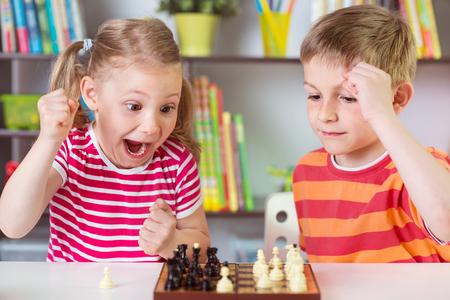 jugando: Dos niños lindos que juegan al ajedrez en casa Foto de archivo