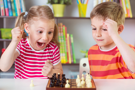 Two cute children playing chess at home