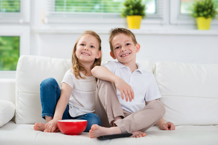 sofa: Little brother and sister watching tv on couch Stock Photo