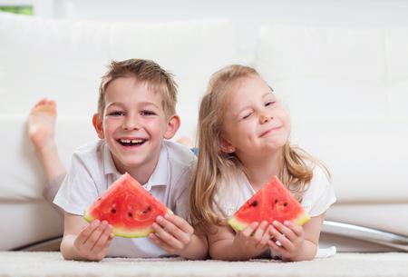 niños comiendo: Los niños pequeños que comen la sandía en el hogar