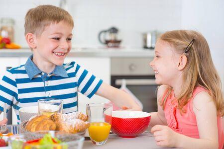 niños desayunando: Dos niños felices que desayunan en la cocina a la mesa
