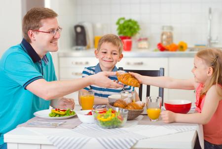 ensalada de frutas: Familia sonriente que come el desayuno juntos en la cocina