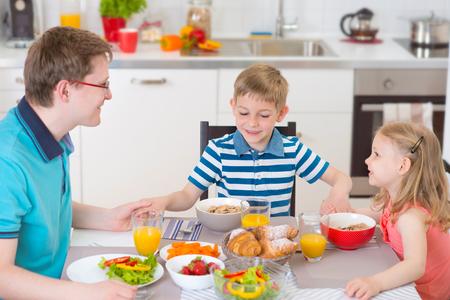 family praying: Familia agradable rezar antes de comer el desayuno juntos