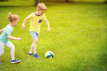 niñas jugando: Deportes familia feliz juega al fútbol en el parque soleado de verano