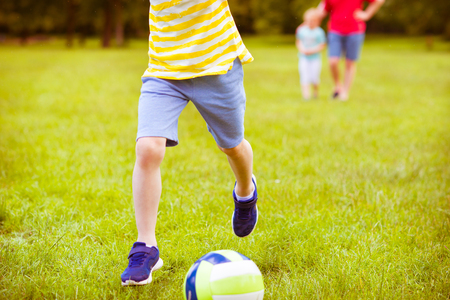 Sporting little boy plays football in sunny park photo