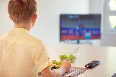 eating dinner: Cute boy child eating at the table in kitchen and watching football Stock Photo
