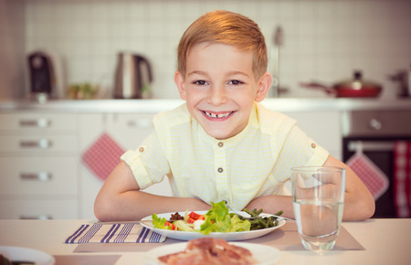 diligent: Young diligent happy boy  at a table eating healthy meal using cutlery