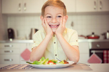 diligent: Young diligent happy boy at a table eating healthy meal Foto de archivo