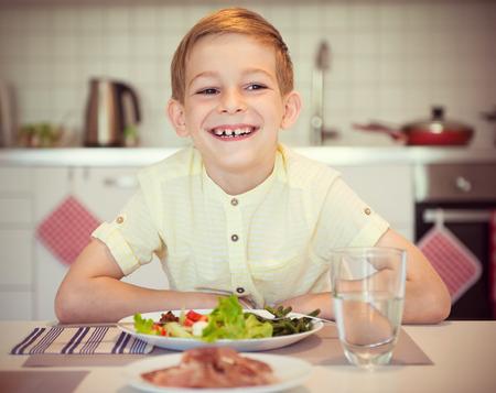 diligente: niño feliz diligente joven en una mesa de comer comida saludable usando los cubiertos