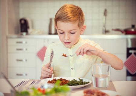 diligente: diligente chico joven en una mesa de comer comida saludable usando los cubiertos