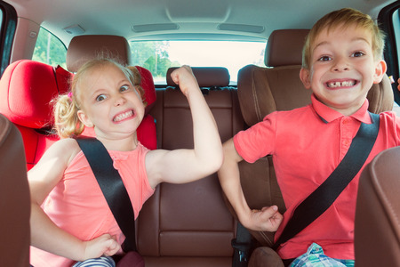Gelukkige kinderen, schattig meisje met haar broer zitten samen in moderne auto vergrendeld met veiligheidsgordels te genieten van familie vakantie reis op zomerweekend