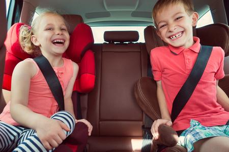 Felices los niños, adorable niña con su hermano sentados juntos en el coche moderno bloqueado con cinturones de seguridad que disfrutan de viaje de vacaciones de la familia el fin de semana del verano