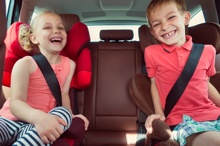 sister: Happy kids, adorable girl with her brother sitting together in modern car locked with safety belts enjoying family vacation trip on summer weekend