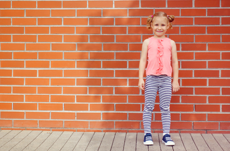 bricks background: Portrait of little kid girl  laughing at a blank empty bricks wall background Stock Photo