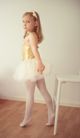 Pretty diligent ballet girl in white tutu practicing a dance number at studio