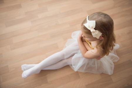 Pretty diligent ballet girl sitting in white tutu at dance studio. Ower view Stock Photo