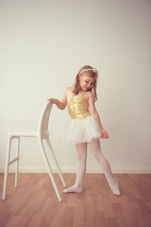 Smiling pretty ballet girl in white tutu practicing a dance number at studio