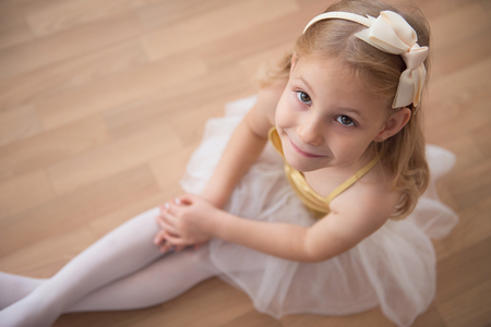 diligent: Portrait of smiling pretty diligent ballet girl sitting in white tutu at dance studio. Ower view Stock Photo