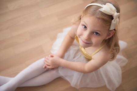 diligente: Retrato de la muchacha sonriente del ballet bastante diligente que se sienta en el tutú blanco en el estudio de baile. Ver ower