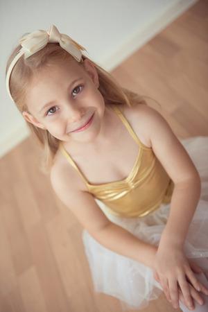 diligente: chica de ballet bastante diligente que se sienta en el tutú blanco en el estudio de baile sola Foto de archivo