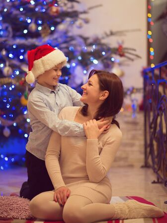 Pretty young mother sitting with her happy son which is in santa hat  photo