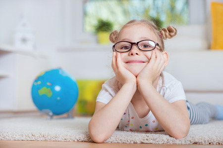 interrior: Portrait of pretty little girl lay on carpet at home with globe on background