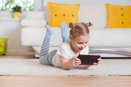 Pretty little girl using a digital tablet, looking and smiling while lying on the floor at home