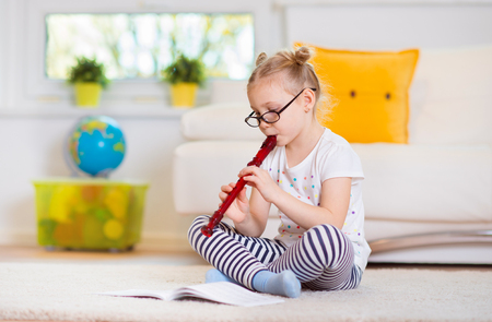 Portrait of pretty little girl with flute on floor at home Imagens