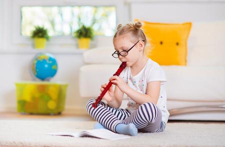 Ritratto di una bella bambina con flauto sul pavimento a casa Archivio Fotografico - 69976629