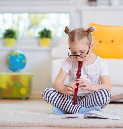 art lessons: Portrait of pretty little girl with flute on floor at home Stock Photo