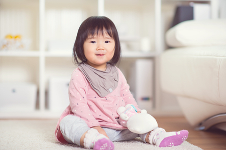 Pretty happy little japanese girl playing on white capet at home