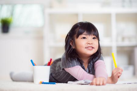 Vrij gelukkig klein Japans meisje liegen en tekenen met potloden op wit capet thuis Stockfoto