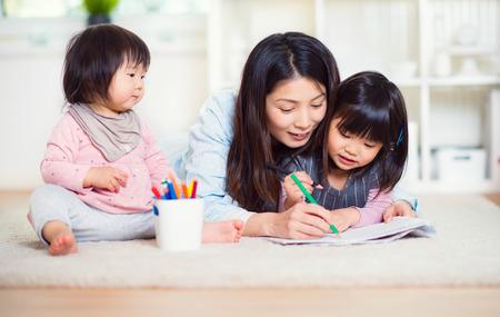 Bastante feliz madre japonesa jugar con sus dos pequeñas hijas lindo en el hogar Foto de archivo - 70370880