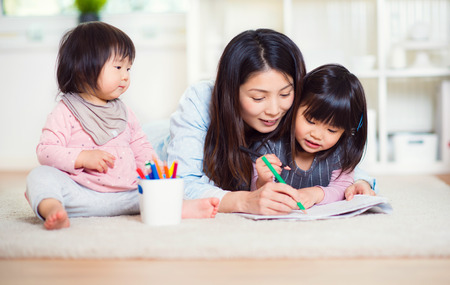 baby playing: Pretty happy japanese mother play with her two cute little daughters at home