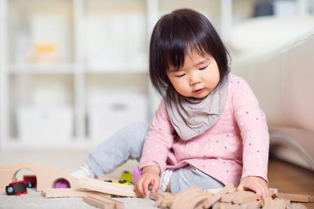 Vrij gelukkig klein Japans meisje spelen op witte capet thuis Stockfoto
