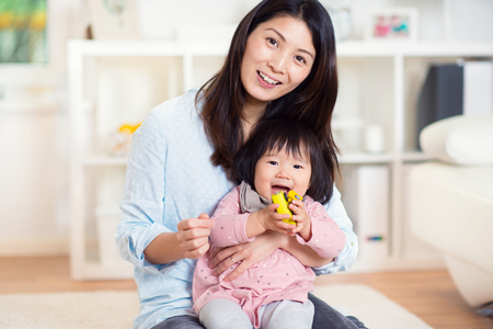 Pretty happy japanese mother play with her cute little toddler daughter at home Banco de Imagens - 70346401