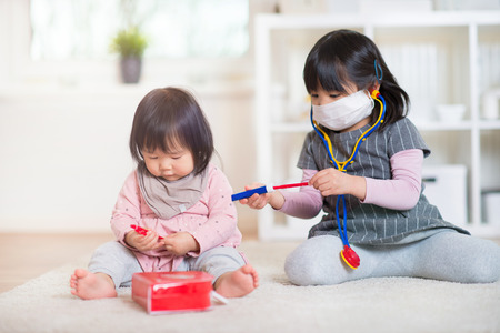 oriental medicine: Two happy japanese sisters playing with medical set on white capet at home